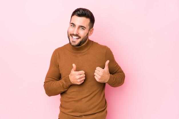 両方の親指を上げる、笑みを浮かべて、自信を持って分離されたピンクの壁に若い男