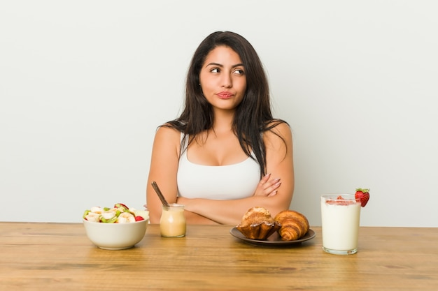 皮肉な表情で見て不幸な朝食を取る若い女性