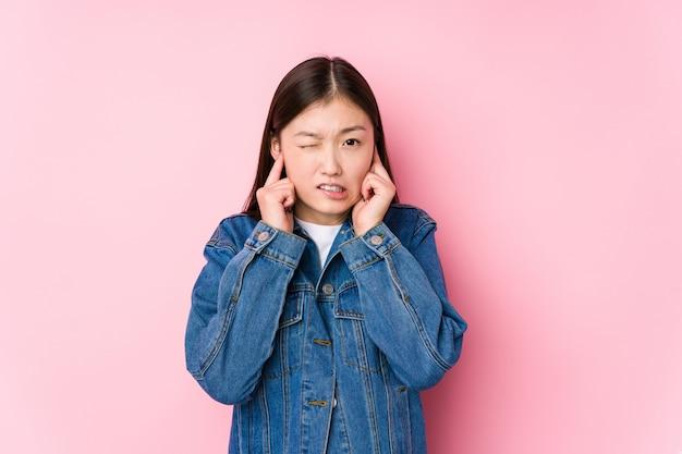 Молодая женщина позирует в розовой стене, изолированные охватывающих уши руками