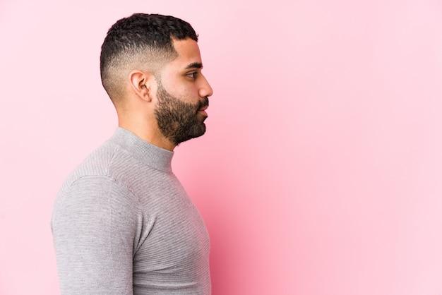 Молодой человек против розовой стены изолированы глядя налево, сбоку позы