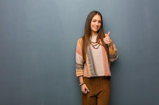 若いヒッピー女性笑顔と親指を上げる