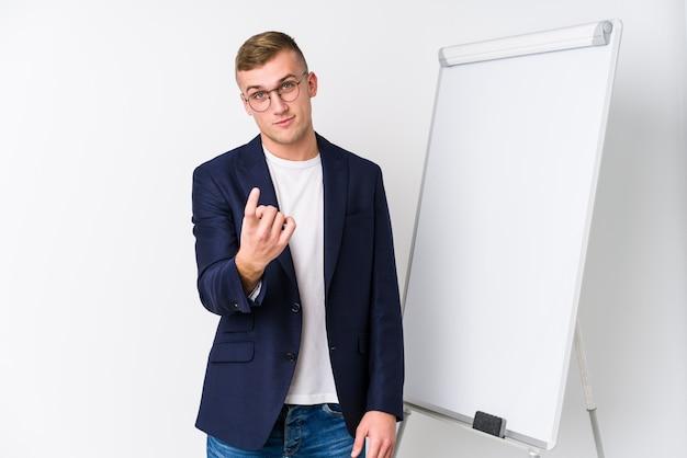 若いコーチング男があなたに指で指しているホワイトボードを見せて、まるで招待が近づくように
