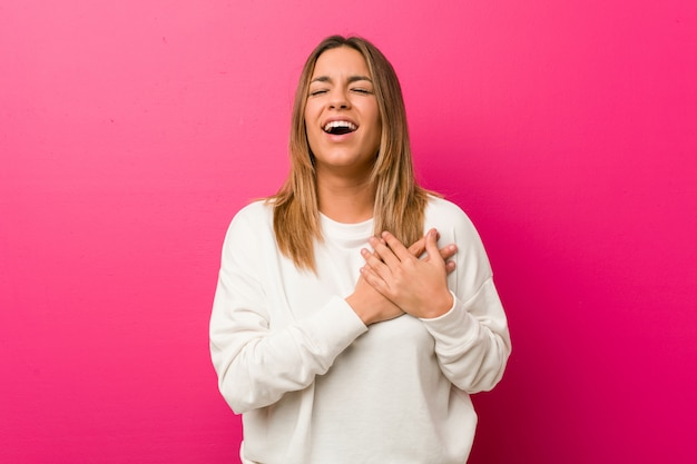 Молодая аутентичная харизматичная женщина у стены смеется, держась за руки на сердце