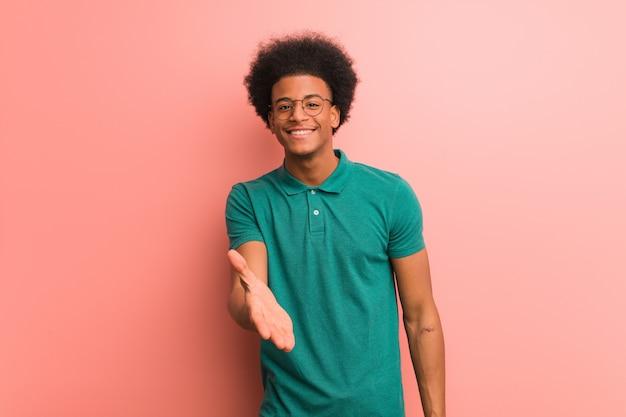 誰かを迎えるために手を差し伸べるピンクの壁の上の若い男