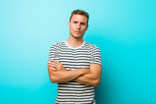 皮肉な表情で見ている不幸な青い壁の若い男