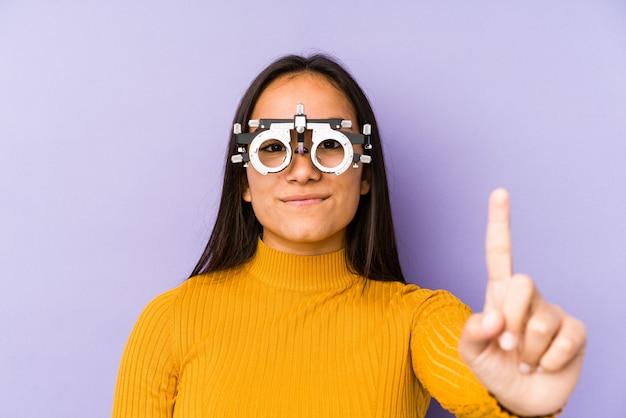 指でナンバーワンを示す検眼メガネで若いインド人女性