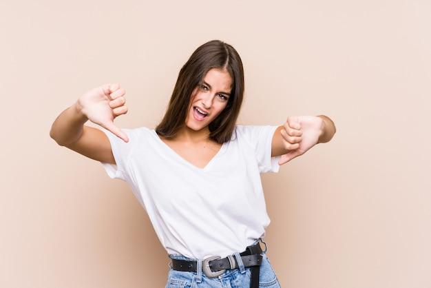 若い白人女性がダウン親指を示すと嫌悪感を表現するポーズします。