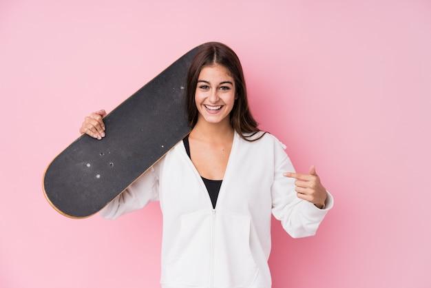 自分を指してスケート人を保持している若い白人のスケーター女性