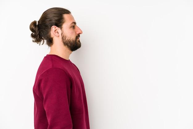 Молодой длинноволосый мужчина на белой стене смотрит налево