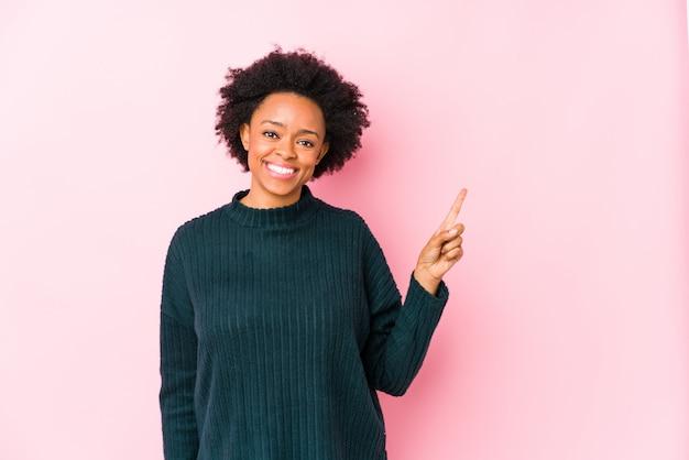 中年のアフリカ系アメリカ人女性は人差し指で元気に指している笑顔のピンクの壁に対して。