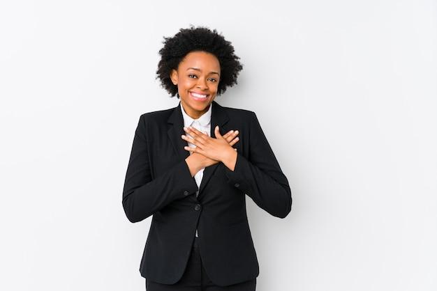 白い壁に中年のアフリカ系アメリカ人ビジネスウーマンはフレンドリーな表情で、手のひらを胸に押し付けます