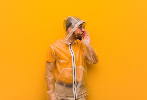 Молодой человек в плаще от дождя