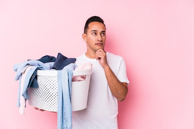 疑わしいと懐疑的な表情で横に見て汚れた服を拾う若いラテン男。