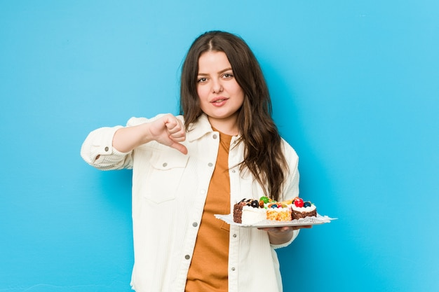 嫌いなジェスチャー、親指ダウンを示す甘いケーキを保持している若い女性
