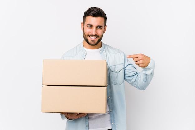 Молодой человек кавказской переезда в новый дом человек, указывая рукой на пустое пространство рубашки, гордый и уверенный