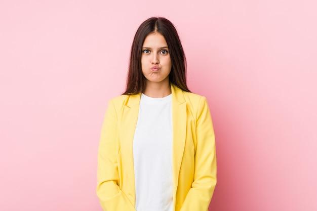 若いビジネス女性の頬を吹く、疲れた表情