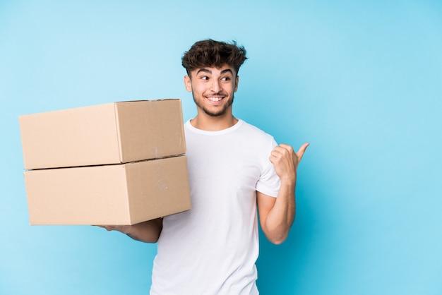 Молодой арабский человек, держащий коробки, указывает пальцем на большой палец, смеясь и беззаботный.