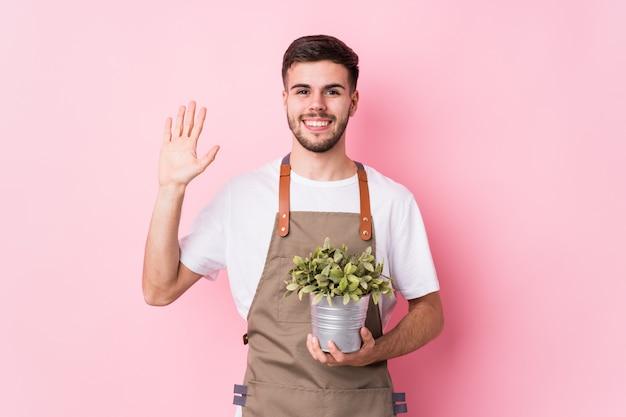 Молодой кавказский садовник человек, держащий растений, улыбаясь веселый показ номер пять с пальцами.
