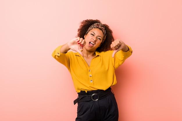 親指を示すと嫌悪感を表現するピンクの壁に若いアフリカ系アメリカ人女性。