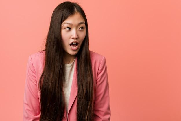 ピンクのスーツを着た若いビジネス中国人女性は、彼女が見た何かにショックを受けています。
