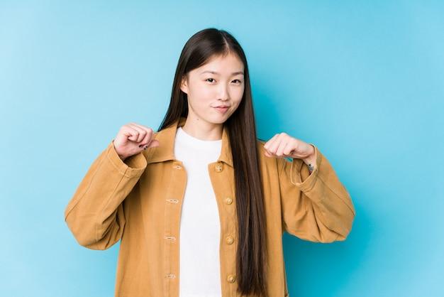 水色の壁でポーズをとる若い中国人女性は誇りに思って、自信を持って、次の例です。