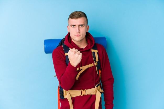 カメラ、積極的な表情に拳を示す若い旅行者白人男。