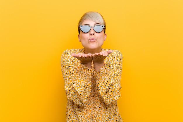 Молодая женщина носить цветочные летней одежды складывать губы и ладонями, чтобы отправить воздушный поцелуй.