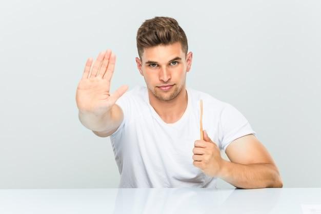 一時停止の標識を示す差し出された手で立っている歯ブラシを保持している若い男
