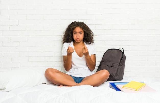 Молодая афро-американская женщина студента на кровати показывая что она не имеет денег.