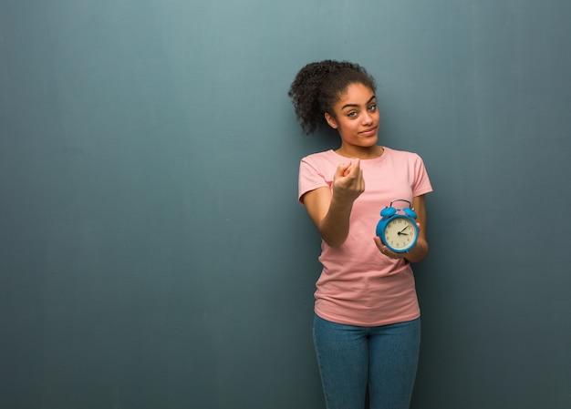 目覚まし時計を保持している若い黒人女性。