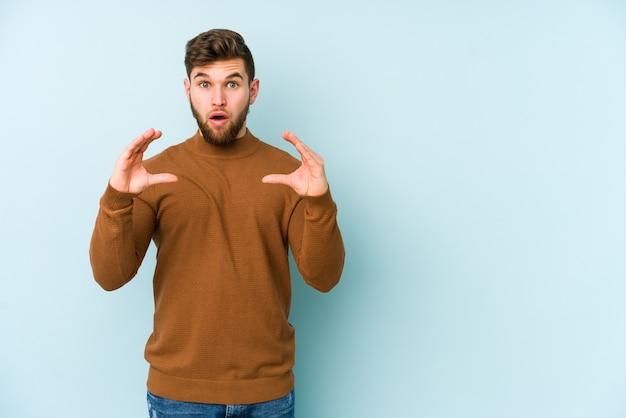 Молодой кавказский человек на голубой стене держа что-то с ладонями