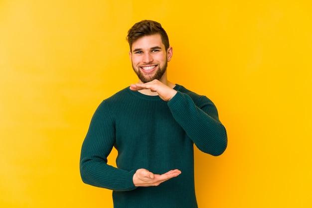 Молодой человек кавказской на желтой стене, что-то держит обеими руками