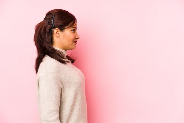 Латинская женщина среднего возраста на розовой стене смотрит влево