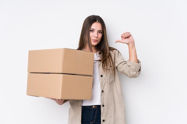 新しい家に引っ越す若い白人女性は、誇りと自信を持っていると感じています。