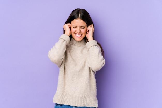 手で耳を覆う紫の壁に分離された若い白人女性。