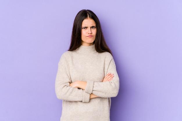 皮肉な表現に不満のある紫色の壁に分離された若い白人女性。