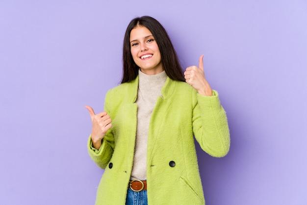 Молодая кавказская женщина изолированная на фиолетовой стене поднимая оба большого пальца руки вверх, усмехающся и уверенно.
