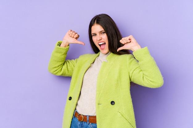 紫色の壁に分離された若い白人女性は誇りに思って、自信を持って、次の例です。