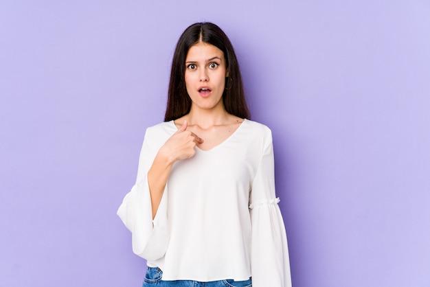 Молодая кавказская женщина изолированная на фиолетовой стене удивила указывать с пальцем, широко улыбаясь.