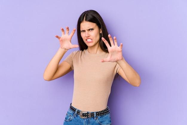 Молодая кавказская женщина изолированная на фиолетовой стене показывая когти имитируя кота, агрессивный жест.