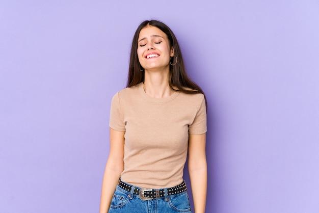 Молодая кавказская женщина изолированная на фиолетовой стене смеется и закрывает глаза, чувствует ослабленным и счастливым.