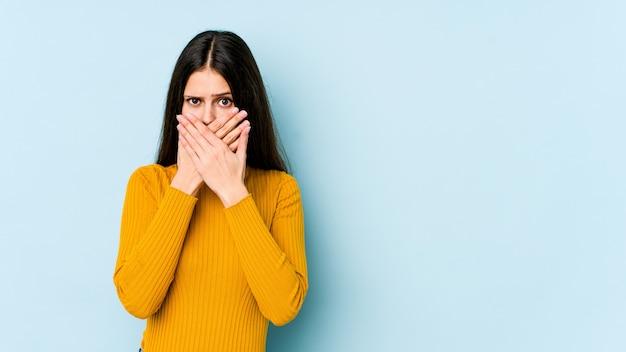 Молодая кавказская женщина изолированная на голубом рте заволакивания стены при руки смотря потревоженный.