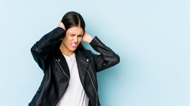 手で耳を覆う青い壁に分離された若い白人女性。
