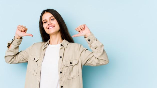 青い壁に分離された若い白人女性は、誇りに思って、自信を持って、次の例です。