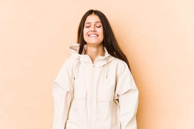 Молодая кавказская женщина изолированная на бежевой стене смеется и закрывает глаза, чувствует ослабленным и счастливым.