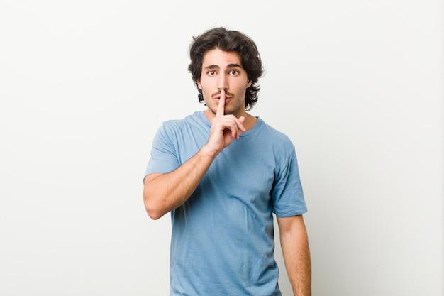 秘密を守るか沈黙を求める白い壁に若いハンサムな男。