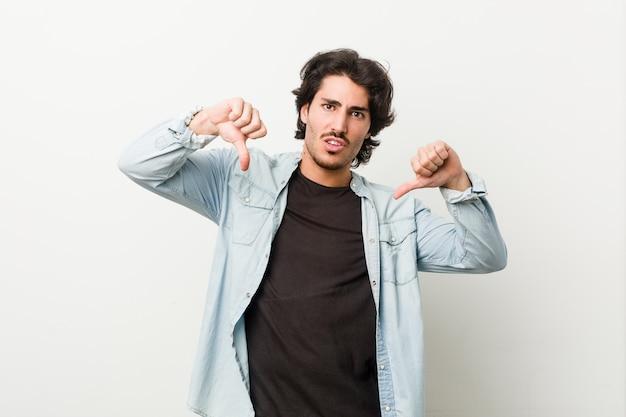 親指を示すと嫌悪感を表現する白い壁に若いハンサムな男。
