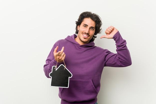 家のアイコンの形を保持している若い男は誇りに思って、自信を持って、次の例です。