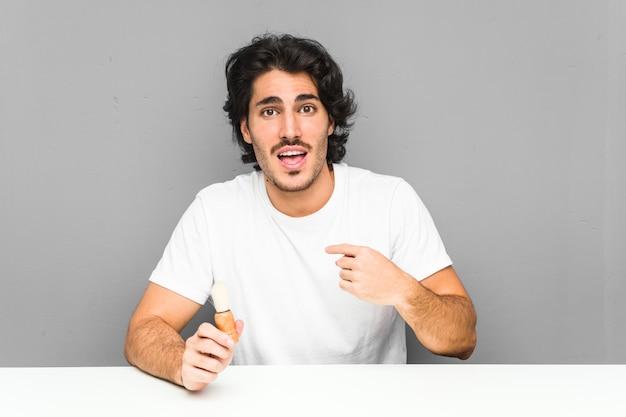 Молодой человек, бреющий бороду, удивленно указывает на себя, широко улыбаясь.
