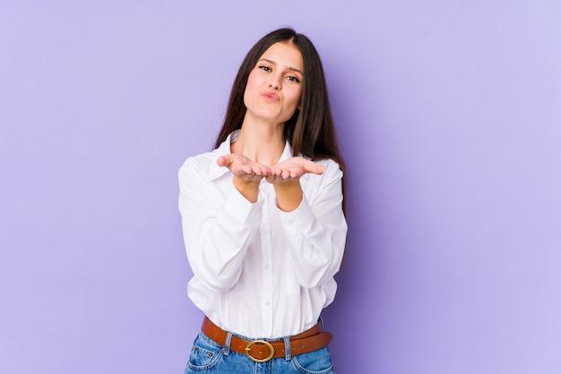 Молодая кавказская женщина на фиолетовой стене складывая губы и держа ладони для того чтобы послать воздушный поцелуй.